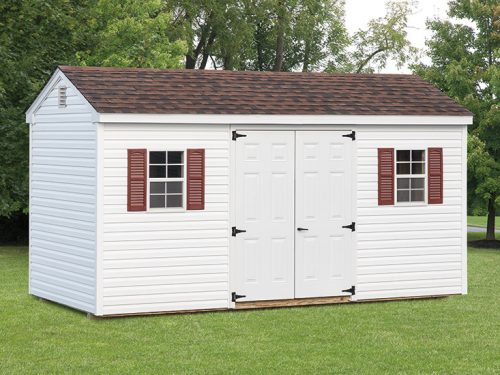 white cottage shed with red shutters