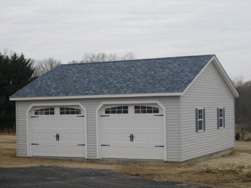 two car garage with asphalt shingle roof